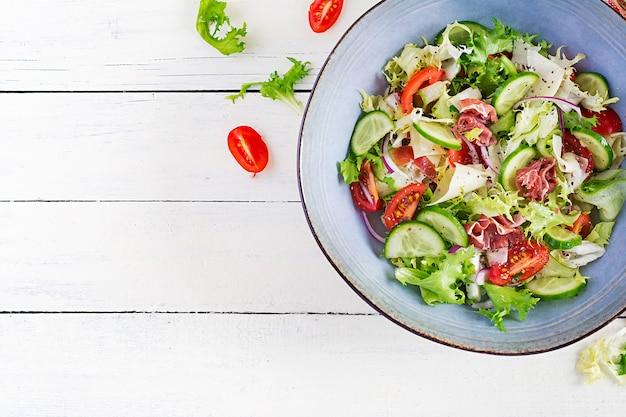 Кетогенный салат с прошутто, помидорами, огурцом, листьями салата, красным луком и сыром в миске. концепция здоровой закуски. кето, палео-еда. вид сверху, над головой, копией пространства