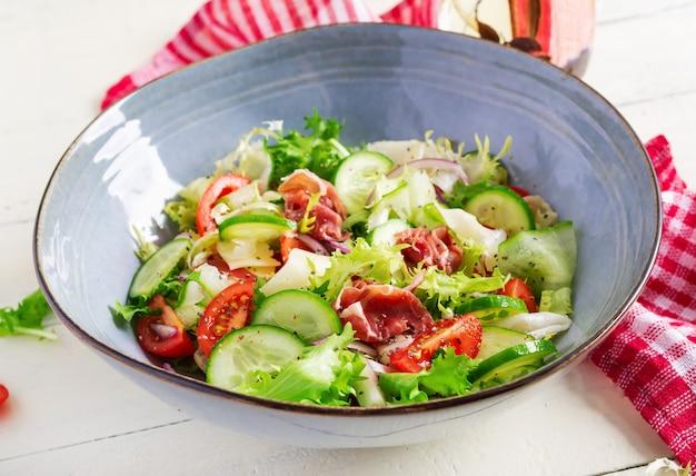Кетогенный салат с прошутто, помидорами, огурцом, листьями салата, красным луком и сыром в миске. концепция здоровой закуски. кето, палео-еда.