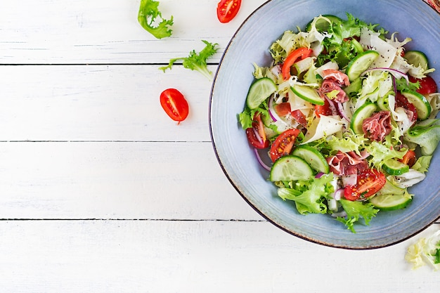 Ketogenic salad with prosciutto, tomatoes, cucumber, lettuce, red onion  and cheese  in  bowl.  concept healthy appetizer. keto, paleo food. top view, overhead, copy space