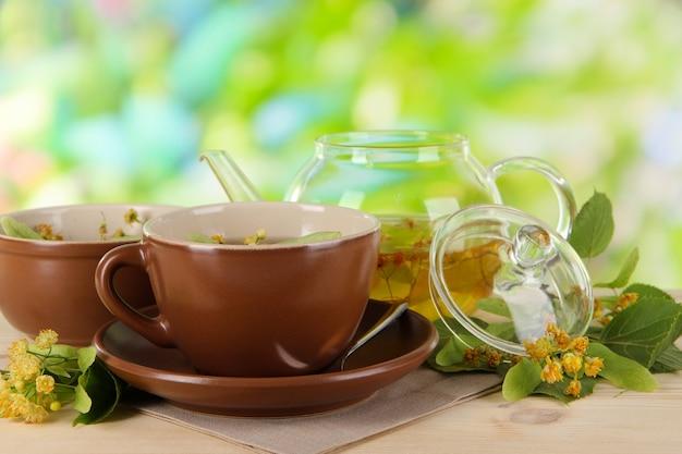 Чайник и чашка чая с липой на деревянном столе на фоне природы