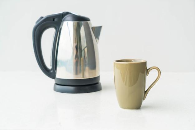 Чайник и чашка на фоне стены