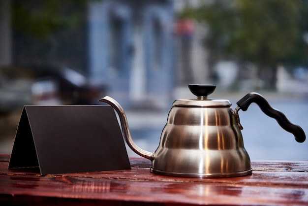 A kettle and a black empty booklet stand on a wooden table on a blurred background