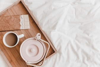 Kettle, chocolate and hot drink on white bedsheet