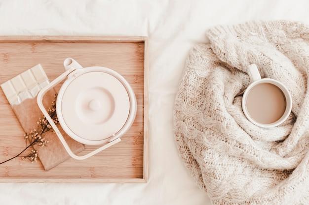 Чайник, шоколад на пищевом столе рядом с горячим напитком в плед