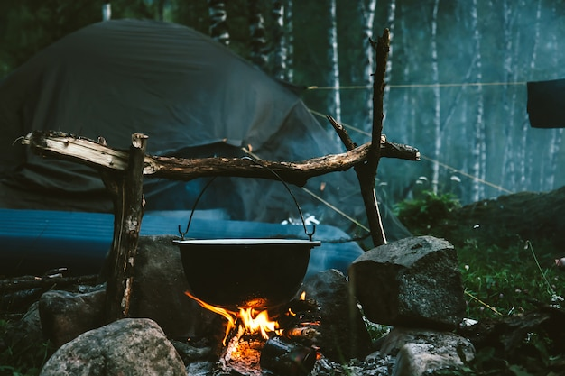 Kettle on fire near tent in forest at night. beautiful campfire in tourist camp into wild. survival in taiga. cauldron above bonfire. smoke from fire among trees. cooking over campfire.