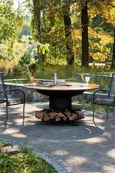 炎のある鋳鉄グリッド付きケトルグリルピット。ラウンドテーブル-調理面。裏庭でのホットバーベキュー
