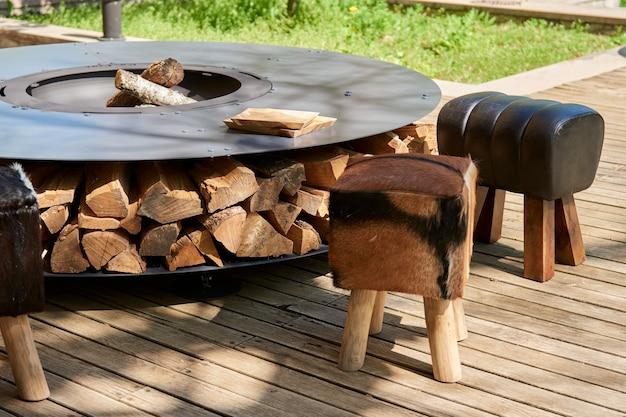 화염이 있는 주철 격자가 있는 주전자 그릴 구덩이 . 둥근 테이블 요리 표면. 뒤뜰에서 뜨거운 바베큐