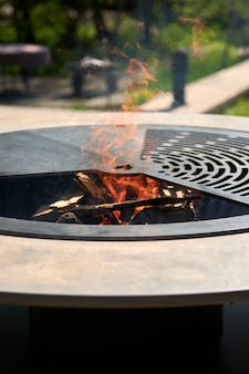 裏庭のテーブル調理面の熱いバーベキューの周りに炎のある鋳鉄グリッド付きのケトルグリルピット