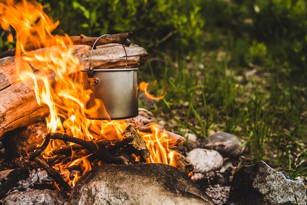 Чайник висит на ветке над огнем