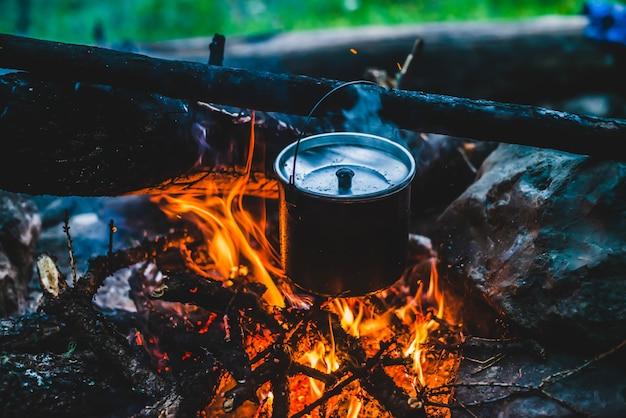 火の上にぶら下がっているすすのやかん。野生の火で料理を調理しています。美しい薪がたき火のクローズアップで燃えます。野生の自然の中での生存。大釜の素晴らしい炎。鍋はキャンプファイヤーの炎でハングします。