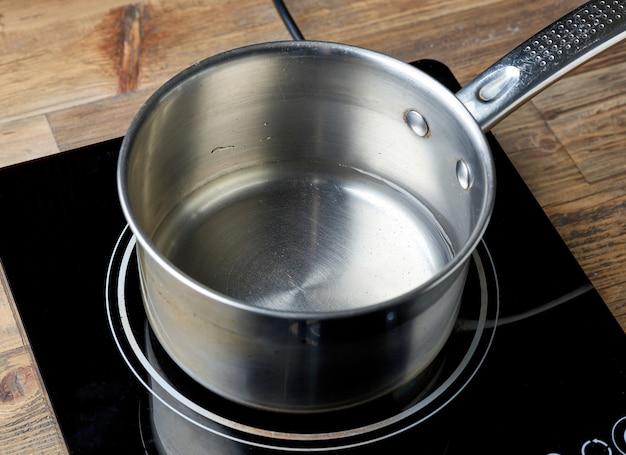 木製の台所のテーブルの電気誘導コンロの水のやかん
