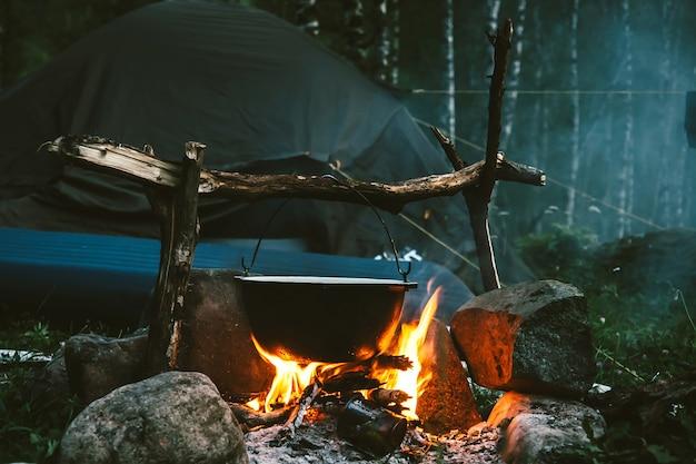 밤에 숲에 텐트 근처 불에 주전자