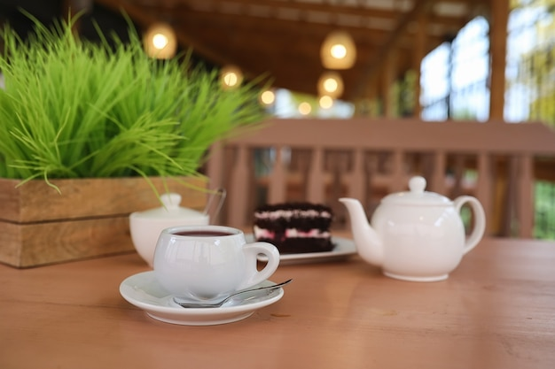 거리 카페에서 음료와 디저트가 있는 주전자. 테이블에 주전자 컵에 차입니다. 카페에서 차와 케이크와 함께 아침 식사.