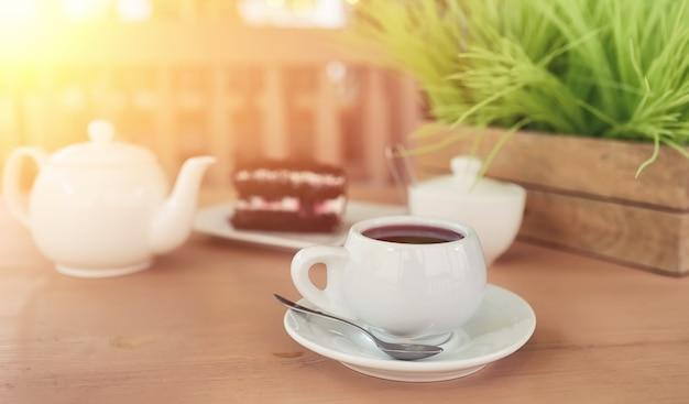 ストリートカフェでドリンクとデザートを持ったケトル。テーブルの上のやかんカップのお茶。カフェでお茶とケーキと一緒に朝食。