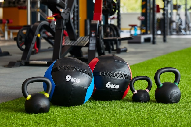 Kettlebells of different sizes and different weights are in row, close-up, gym