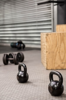 Kettlebells and dumbbells on the floor of a gym