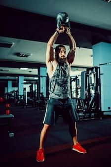 Фитнес kettlebells качели упражнения человек тренировки в тренажерном зале