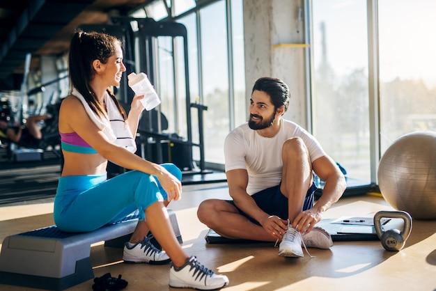 Привлекательная молодая пара фитнеса, отдыхая на черном циновке и степпере с мячом kettler и перчатками рядом с ними в тренажерном зале.