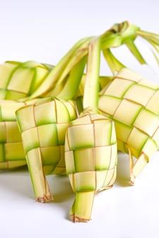Кетупат, изолированные на белом фоне. типичное блюдо из риса, завернутого в обертку из заплетенных молодых кокосовых листьев.