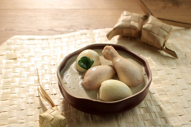 Ketupat opor ayam lebaran is chicken soup cooked in coconut milk from indonesia served with lontong and sambal. popular dish for lebaran or eid al-fitr, square picture. serving on a brown bowl