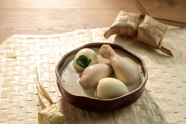 Кетупат опор аям лебаран - это куриный суп, приготовленный на кокосовом молоке из индонезии, подается с лонтонгом и самбалом. популярное блюдо для лебарана или ид аль-фитр, квадратная картина. сервировка в коричневой миске