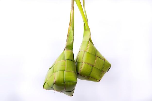 Кетупат (рисовые клецки) - традиционное блюдо индонезии во время ид мубарак, изолированное на белой поверхности.