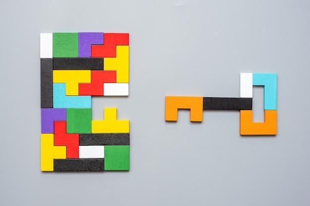 기하학적 다채로운 나무 퍼즐 조각의 키와 열쇠 구멍 모양.