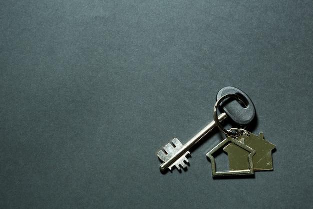 검정색 배경에 열쇠가 있는 집 모양의 열쇠 고리. 건물, 디자인, 프로젝트, 새 집으로 이사, 모기지, 보증금, 임대 및 부동산 구매. 복사 공간