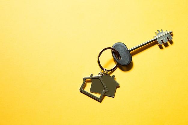 노란색 배경에 열쇠가 있는 목조 주택 모양의 열쇠 고리. 건물, 디자인, 프로젝트, 새 집으로 이사, 모기지, 부동산 임대 및 구매. 복사 공간