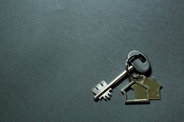 Key chain in the shape of house with key on a black background. building, design, project, moving to new home, mortgage, deposit, rent and purchase real estate. copy space