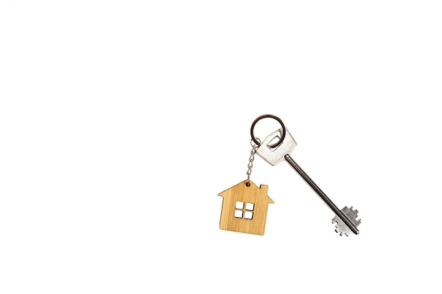 Key chain in the shape of wooden house with key on a white background, isolate. building, design, project, moving to new home, mortgage, rent and purchase real estate, booking. copy space