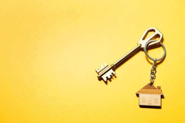 Key chain in the shape of wooden house with key on a yellow background. building, design, project, moving to new home, mortgage, rent and purchase real estate. copy space