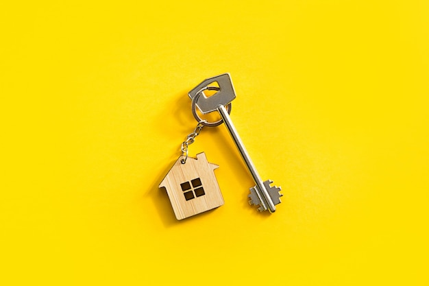 Key chain in the shape of wooden house with key on a yellow background.