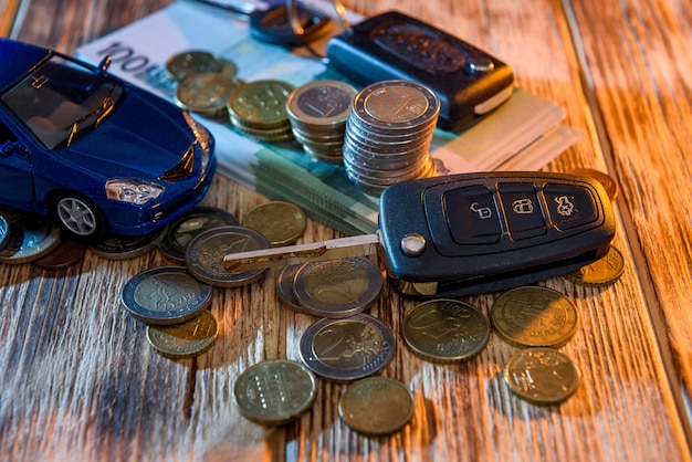Key from car and toy car at euro banknotes with coins