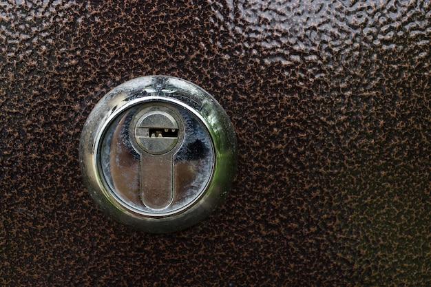 A key hole on the brown door. typical door lock. a metallic keyhole on a metal door. key hole detail.