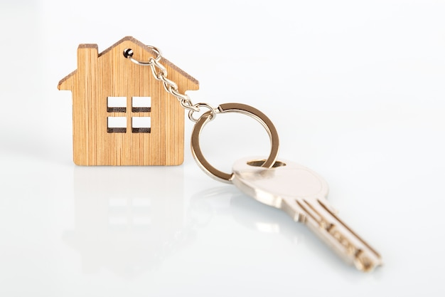 A key on a house shaped wooden keychain