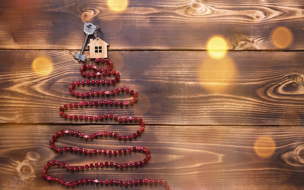 Key to the house with a keychain on top of christmas tree made of red square beads