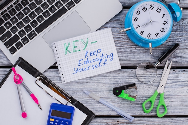 Ключ - сохранить концепцию образования. предметы для обучения и изучения на белом деревянном столе. плоский вид сверху.