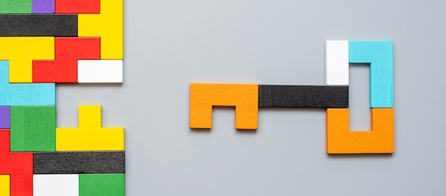 Key and keyhole shape of geometric colorful wood puzzle pieces.