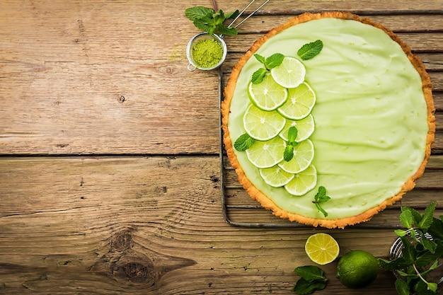 Key lime pie с несколькими лаймами и мятой на деревянной поверхности, вид сверху с копией пространства.