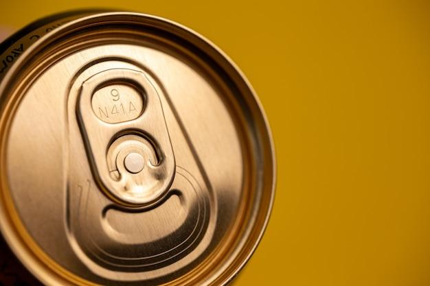 노란색 배경에 금속 맥주 캔의 키.