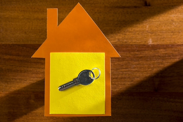 Key for real estate on the background of a house made of cardboard