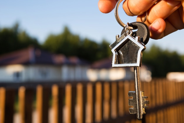 Key ring with keychain house in hand. background of fence and cottage. moving to a new home, mortgage, buying real estate, renting and booking housing, dream of living  in the village. copy space