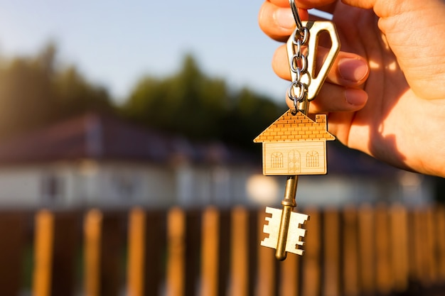 Key ring with keychain house in hand of fence and cottage. moving to new home, mortgage, buying