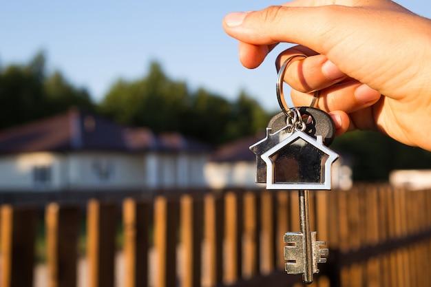 손에 키체인 하우스가 있는 키 링. 울타리와 오두막의 배경입니다. 새 집으로 이사, 모기지, 부동산 구입, 임대 및 예약, 마을에서 살기의 꿈. 복사 공간