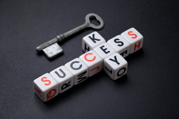 Key to success, old vintage key on top and letter dice spelling key in vertical and success