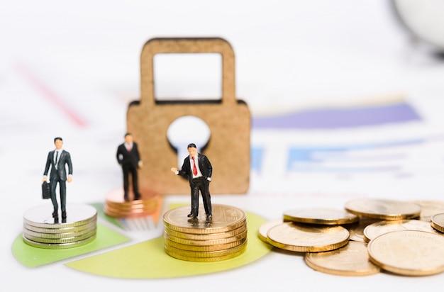 Ключ к завоеванию большой доли рынка, миниатюрные деловые люди стоят на золотых монетах с фоном диаграммы.
