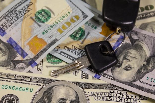 アメリカの100ドル紙幣の背景に車のキーリング付きのキー。車の売買のコンセプト