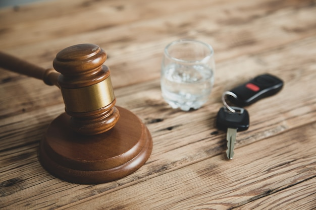 Key with glass and judge gavel on desk