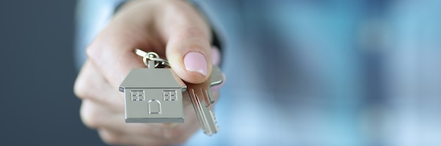 Key with house keychain is pulled forward getting loan for housing construction concept
